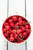 Fresh wet cherries in a bowl on white planked wood table from above Stock Image
