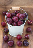 Fresh wet cherries  in a white bucket on the wooden background Stock Photo