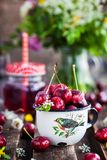 Fresh wet cherry in enamel metal mug Stock Images