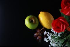 Fresh wet fruits : lemon, green apple and grapes with decoration  on black background Stock Image