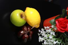 Fresh wet fruits : lemon, green apple and grapes with decoration  on black background Stock Photos