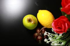Fresh wet fruits : lemon, green apple and grapes with decoration isolated on black background Royalty Free Stock Photos