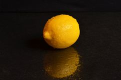 Fresh wet lemon on a black background. Fresh and wet lemon on a black background Royalty Free Stock Image