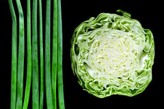 Fresh wet onion greens and cabbage isolated on black Stock Photo