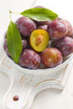 Fresh wet plums with leaves in the bowl Royalty Free Stock Images