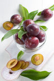 Fresh wet plums with leaves in the bowl on the vin Royalty Free Stock Photos