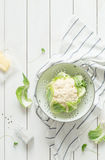Fresh wet raw cauliflower in a strainer on rustic white royalty free stock images