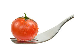 A fresh wet tomato on a fork Royalty Free Stock Photos