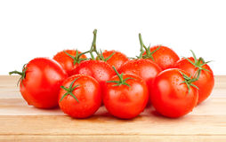 Fresh wet tomatoes on a cutting board wooden Stock Image