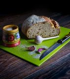 Fresh wheat bread, garlic, a wooden saltcellar with salt, a green board for cutting bread, a knife. All this lies on a dark wooden royalty free stock images