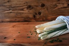 Fresh white asparagus and chive. On rustic wooden background royalty free stock photography