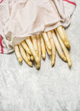 Fresh white asparagus with wet kitchen towel on light wooden background, top view Royalty Free Stock Photos