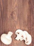 Fresh white champignon mushrooms close up on wooden background. Fresh white champignon mushrooms close up on dark brown wooden background with copyspace. Flat Royalty Free Stock Image