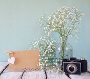 Fresh white flowers, heart next to vintage empty card and old camera over wooden table. Stock Photos