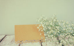 Fresh white flowers next to vintage empty card over wooden table. vintage filtered and toned image royalty free stock image