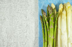 Fresh white and green asparagus on the blue board. And grey background Stock Photos