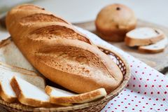 Fresh white loaf of bread and cupcakes royalty free stock images