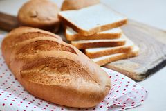 Fresh white loaf of bread, toasts and cupcakes royalty free stock photo