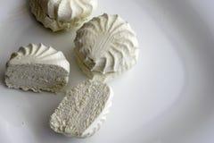 Fresh white marshmallow lies on white plate stock images