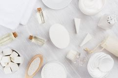 Fresh white natural cosmetics - white cream, oil, towel and bath accessories on soft light white wood table, flat lay. Fresh white natural cosmetics - white royalty free stock images