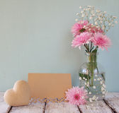 Fresh white and pink flowers, heart next to vintage empty card over wooden table stock photos