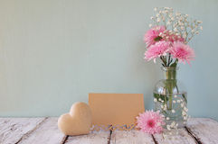 Fresh white and pink flowers, heart next to vintage empty card over wooden table royalty free stock photography