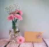 Fresh white and pink flowers, heart next to vintage empty card over wooden table. vintage filtered and toned image royalty free stock image