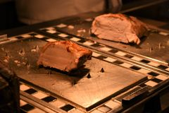 An appetising joint of cooked carved roast pork and turkey meat in the background. Fresh white pork meat for a traditional Sunday lunch or dinner with a turkey stock image