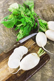 Fresh white radish bunch with green leaves on wooden background Royalty Free Stock Photography