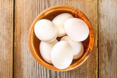 Fresh white raw chicken eggs with parsley on an old wooden table. Fresh white raw chicken eggs with parsley on an old wooden table royalty free stock image