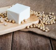 Fresh white soft Japanese tofu on wooden plate with soy bean on gunny sack cloth royalty free stock photo