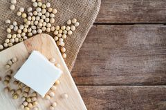 Fresh white soft Japanese tofu on wooden plate with soy bean on gunny sack cloth royalty free stock images