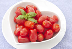 Fresh whole baby plum tomatoes. Fresh baby plum tomatoes in a heart shaped bowl, with a sprig of basil in the top left corner Stock Image
