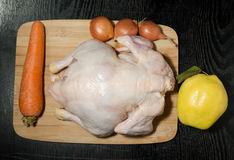 Fresh whole chicken with fruit and vegetables is prepared for co. Oking on a light wooden cutting board on a black table Royalty Free Stock Images