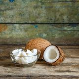 Fresh whole and half coconuts with coconut shreds Royalty Free Stock Photo