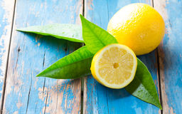 Fresh whole and cut half lemons wish leaves on wooden old blue background Royalty Free Stock Photography