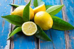 Fresh whole and cut half lemons wish leaves on wooden old blue background Royalty Free Stock Image