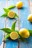 Fresh whole and cut half lemons wish leaves on wooden old blue background Stock Images