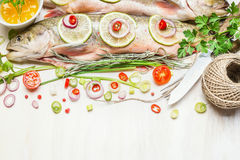 Fresh whole fish with chopped ingredients for tasty cooking Royalty Free Stock Images