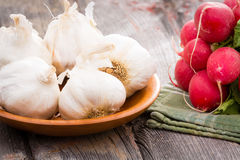 Fresh whole garlic bulbs with radishes. Close up view of healthy fresh whole garlic, bulbs for an aromatic pungent seasoning used in cooking with a bunch of Stock Photo