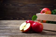 Fresh whole and half red apples. On wooden background stock photography
