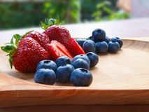 Strawberries and blueberries on wooden bowl. royalty free stock photo