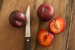 Fresh whole and halved plums Royalty Free Stock Image