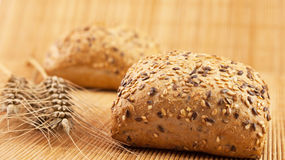 Fresh whole meal bread with seeds on wooden background and wheat. Fresh whole meal bread with seeds Stock Image