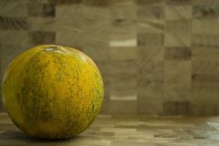 Fresh, whole melon on a wooden background. Free space for text. Side view stock photography