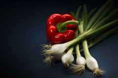 Fresh whole red bell pepper with spring onions Royalty Free Stock Photography