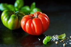 Fresh ripe red tomato with water droplets. Fresh whole ripe red tomato with water droplets on a black surface with copy space and fresh basil, coarse salt and Royalty Free Stock Image