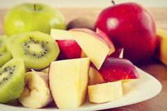Fresh whole and sliced apple and kiwi closeup, gently toned Royalty Free Stock Photos