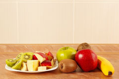 Fresh whole and sliced fruit on kitchen table Stock Photo