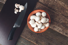 Fresh whole and sliced mushrooms on a cutting board near knife  wooden background.  white champignon in brown bowl. Top view. Copy Royalty Free Stock Image